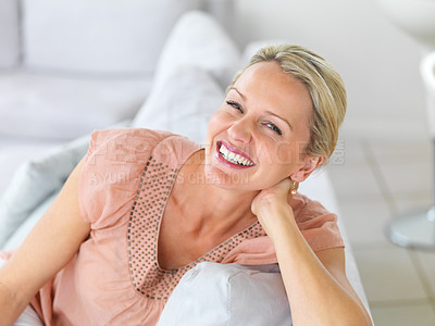 Buy stock photo Portrait of a happy mature woman laughing while sitting on the couch at home