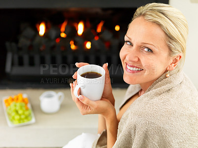 Buy stock photo Portrait of a mature woman by the fireplace having a hot cup of coffee