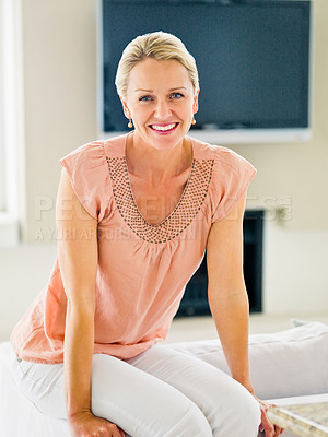 Buy stock photo A lovely middle aged woman smiling while sitting at home
