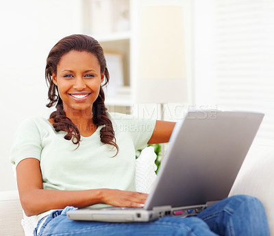 Buy stock photo Happy African American young woman smiling at you while using a laptop at home - copyspace