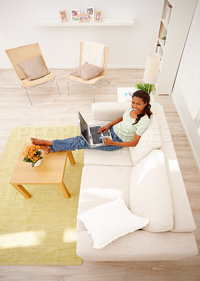 Buy stock photo Top view of a relaxed African American woman sitting on sofa and using laptop
