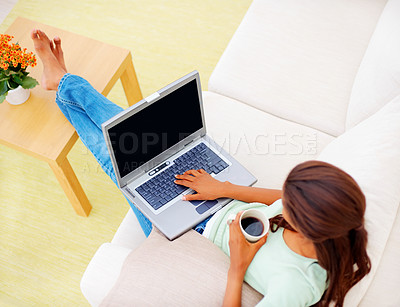 Buy stock photo Top view of an African American woman on sofa using a laptop while having cup of tea