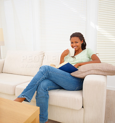 Buy stock photo Cute African American female relaxed at home, having a cup of coffee while reading book