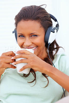 Buy stock photo Cute African American woman drinking a tea, listening to music on the headphones