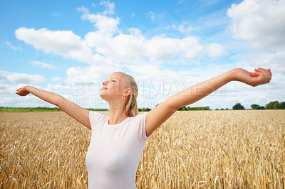 Buy stock photo An attractive young woman standing in a crop field with her arms raised and eyes closed - copyspace