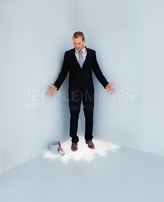Buy stock photo Full length of a handsome business man standing trapped at the corner of a fresh painted floor