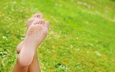 Buy stock photo A relaxed woman's legs on a green grass background