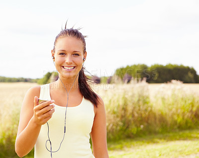 Buy stock photo Portrait of a cute young female listening to an mp3 alongside a sunny summer field - copyspace