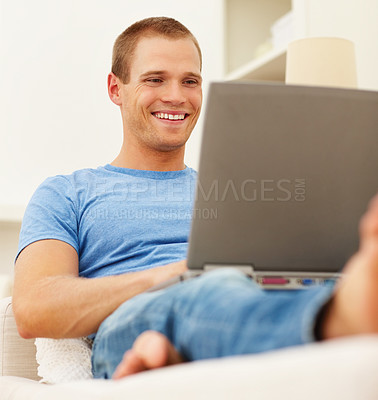 Buy stock photo An attractive young boy working on a laptop while sitting at home