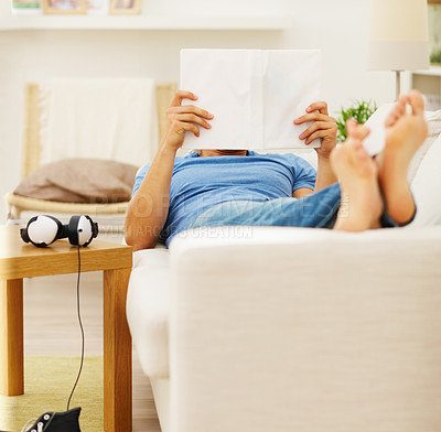 Buy stock photo Young man lying on a couch reading a book at home