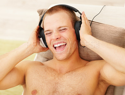 Buy stock photo Closeup of a shirtless young man listening to music on the headphones