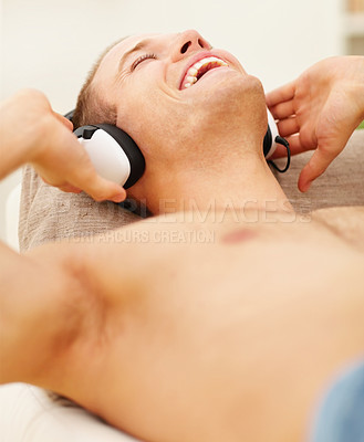 Buy stock photo Young guy enjoying music on the headphones while in the comfort of his home