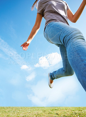 Buy stock photo Upward view of a woman running out of frame over grass with bright blue sky and large copyspace