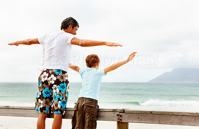 Buy stock photo Happy father and son standing on the railing at a beach with their hands outstretched