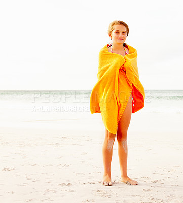 Buy stock photo Full length of a young girl in a bikini covered in a yellow towel at the sea shore