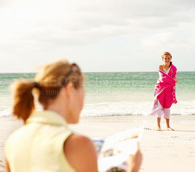 Buy stock photo Happy young girl standing covered in a towel at the beach, mother reading a magazine