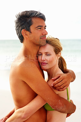 Buy stock photo Happy couple hugging each other and romancing at the sea shore