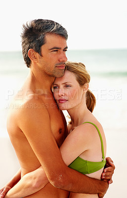 Buy stock photo Romantic couple embracing eachother while at the sea shore