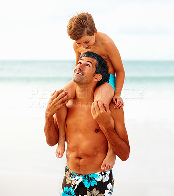 Buy stock photo Mature man carrying his son on his shoulders while at the beach, looking at eachother
