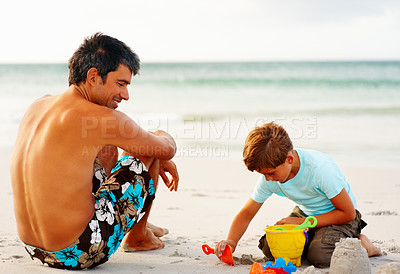 Buy stock photo Happy father and son on a beach vacation, boy making sand castle