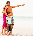 Happy family on their beach vacation, father pointing away