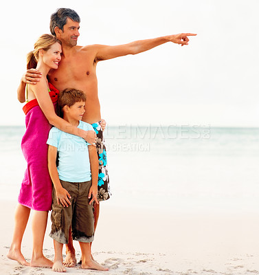 Buy stock photo Portrait of a family smiling while at the sea shore, father pointing away
