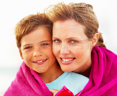 Buy stock photo Cute small boy being embraced by mother while on their beach vacation