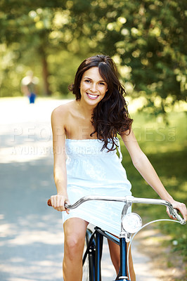 Buy stock photo Cropped shot of an attractive young woman cycling in the park