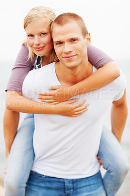 Buy stock photo Piggyback: Young couple in a playful mood outdoors