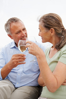 Buy stock photo Senior couple celebrating their retirement with a champagne glass, outdoors