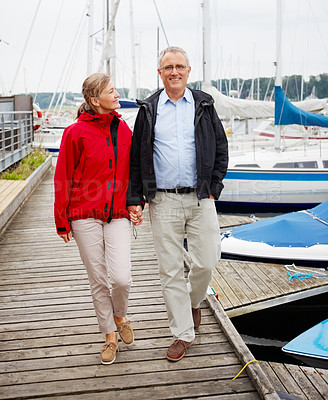 Buy stock photo Full length image of a mature couple strolling on the footbridge by the bay