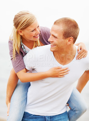 Buy stock photo Happy young male piggybacking his girlfriend, outdoors