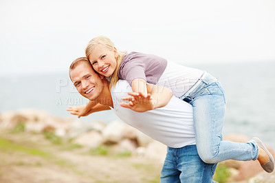 Buy stock photo Happy young couple enjoying themselves out in the open, female on man's back