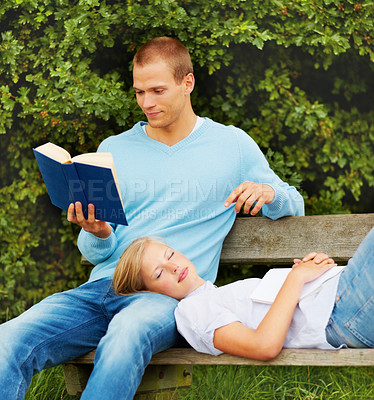Buy stock photo Couple relaxing in the garden, young man reading a book while his girlfriend resting on his lap