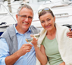 Happy senior couple having champagne while on sailboat