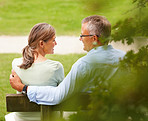 Rear view of an old couple sitting on a bench at the park