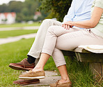 Low section of a couple sitting on a bench at a park