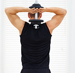 Rear view of a young guy exercising his triceps with a dumbbell