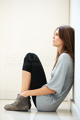 Buy stock photo Young woman sitting on the floor and thinking  - C