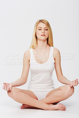 Buy stock photo A pretty young woman sitting in the lotus position while isolated on white
