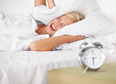 Buy stock photo An attractive young woman covering her ears as her alarm rings