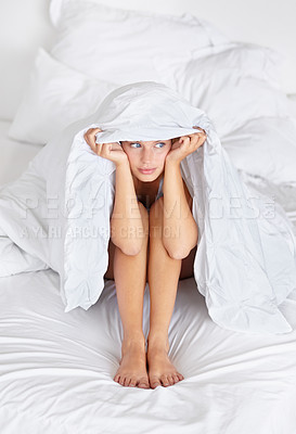 Buy stock photo A pretty young woman pondering whether to face the day or stay in bed