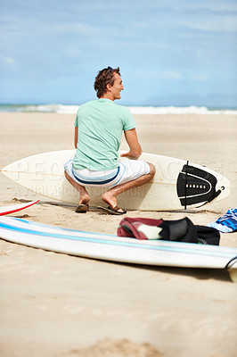 Buy stock photo Rear view of a young surfer crouched on the beach watching the waves