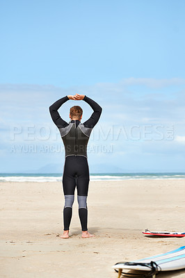 Buy stock photo A surfer putting on his wetsuit at the beach