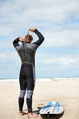 Buy stock photo A young man in a wetsuit getting ready for surfing