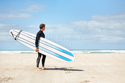 Buy stock photo Shot of a surfer carrying his board while looking out at the ocean