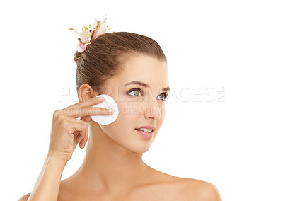 Buy stock photo Head and shoulders studio shot of a young woman cleansing her skin isolated on white