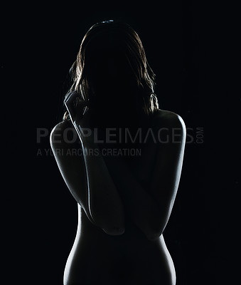 Buy stock photo Silhouette of a naked young woman against a dark bakground