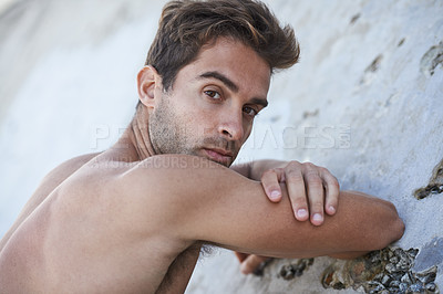 Buy stock photo Portrait of a handsome  bare-chested young man leaning against a rock