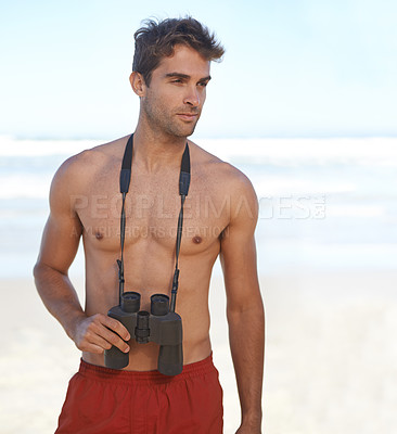 Buy stock photo A handsome young lifeguard at the beach